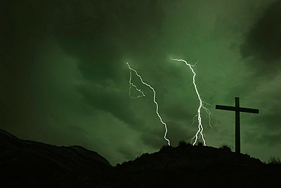 Cross with lightening in background - p4421424f by Design Pics