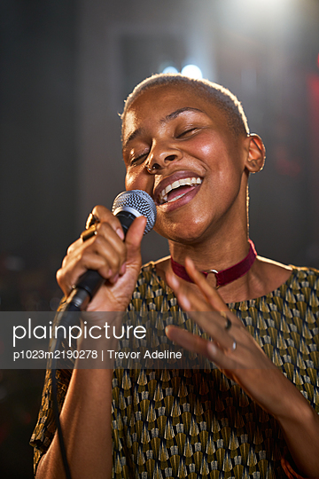 Young female musician singing into microphone - p1023m2190278 by Trevor Adeline