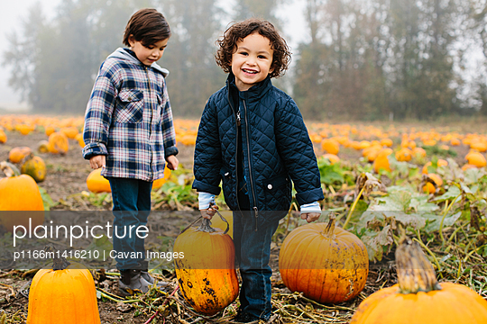 Portrait of happy boy carrying pumpkins while standing with brother at farm during winter - p1166m1416210 by Cavan Images