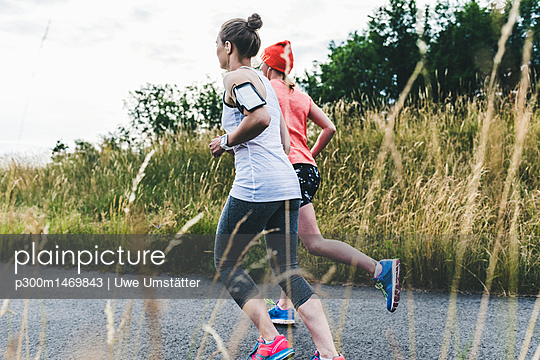 Two women running in the countryside - p300m1469843 by Uwe Umstätter