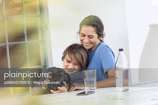 Mother and daughter sitting at home, daughter checking camera - p300m2155570 by Maya Claussen