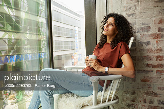 Thoughtful female professional with coffee cup sitting on chair by window - p300m2293763 by Rainer Berg