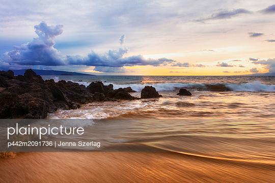Dramatic beach sunset with soft water and lava rocks; Makena, Maui, Hawaii, United States of America - p442m2091736 by Jenna Szerlag