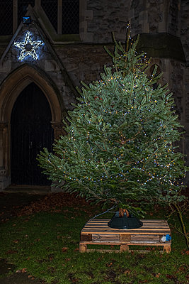 Christmas tree with fairy lights in front of church - p1291m2245119 by Marcus Bastel