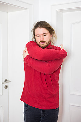 Man in red sweater hugs himself, portrait - p1621m2231953 by Anke Doerschlen