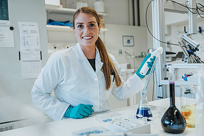 Smiling woman pipette while standing at laboratory - p300m2226190 by Mareen Fischinger