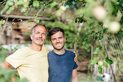 Confident father with arm around son standing under tree in backyard - p300m2277011 by Gustafsson