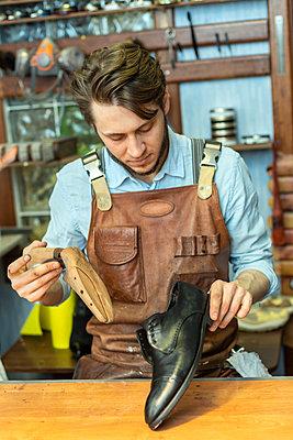 Male entrepreneur holding shoe stretcher while looking at shoe at workshop - p300m2282560 by Vladimir Godnik