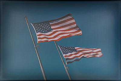 Two United States flags blowing in the wind. - p397m1183470 by Peter Glass