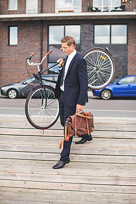 Full length of businessman carrying bicycle while walking on steps - p426m977545f by Maskot