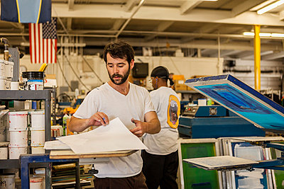 Worker picking up paper in screen print workshop - p924m825944f by heshphoto