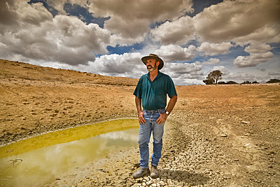 Sheep farmer standing at waterhole during drought - p1125m2073230 by jonlove