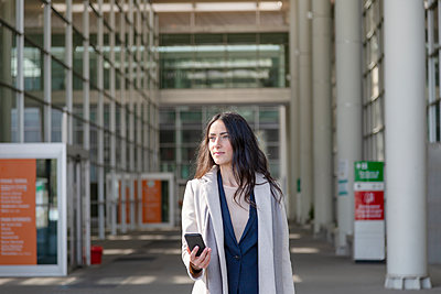 Young businesswoman holding mobile phone while looking away - p300m2281711 by Emma Innocenti