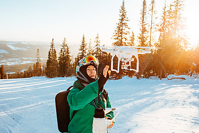 Man with a drone during winter in Osterdalen, Norway - p352m1523660 by Benjamin Rudström