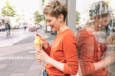 Woman eating ice cream in front of shop, Cologne, Nordrhein-Westfalen, Germany - p429m2077848 by Tamboly