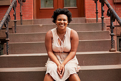 Portrait of smiling Black woman sitting on urban front stoop - p555m1303260 by Granger Wootz