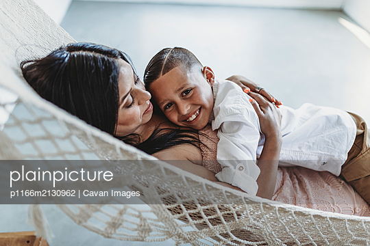 Mother and young son cuddling while laying in hammock in studio - p1166m2130962 by Cavan Images