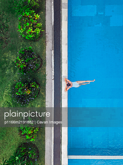 Aerial view of attractive woman floating over water at resort - p1166m2191882 by Cavan Images