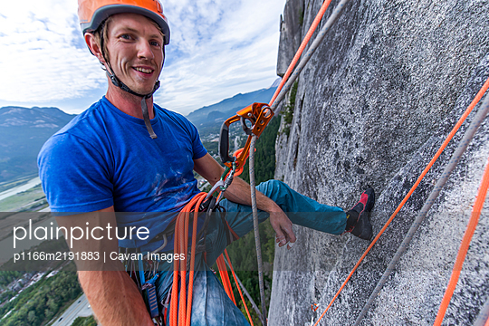 Man resting while rock climbing hanging on rope with ascender - p1166m2191883 by Cavan Images