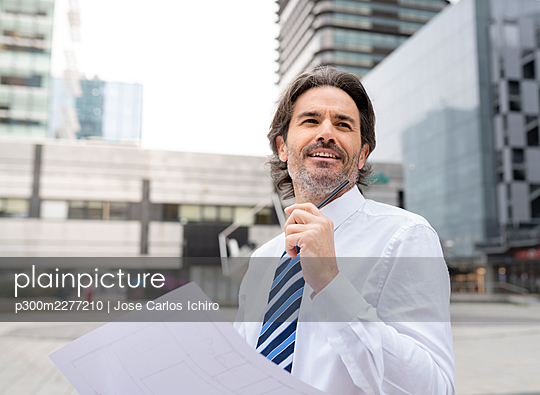 Smiling male architect holding blueprint while standing in office park - p300m2277210 by Jose Carlos Ichiro