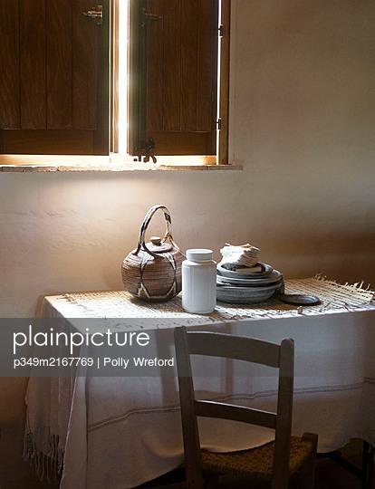 Chair at table below window with closed shutters in Sicilian home - p349m2167769 by Polly Wreford