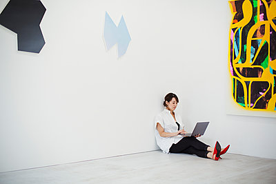 Woman with short black hair wearing white shirt, black trousers and red high heel shoes sitting on floor i art gallery, holding laptop. - p1100m1531068 by Mint Images