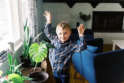 Little happy boy admiring his propagated monstera philodendron. - p1166m2174300 by Cavan Images