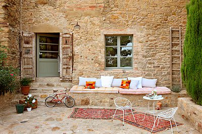 Courtyard with delicate terrace chairs and table in front of masonry bench on outside wall of Italian farmhouse - p1183m996978 by Hausmann, Jose-Luis