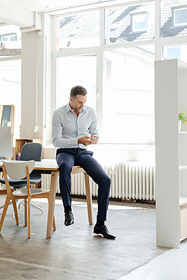 Businessman in office looking at cell phone - p300m1499313 by Kniel Synnatzschke
