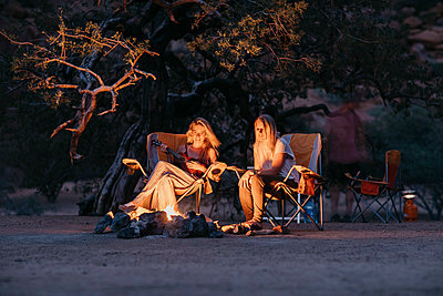 Namibia, friends sitting at campfire playing guitar - p300m2081072 von letizia haessig photography