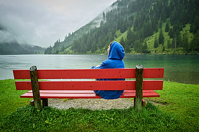 Woman wearing blue hood sitting on bench at lakeshore while looking at mountains - p300m2220599 by Dirk Kittelberger