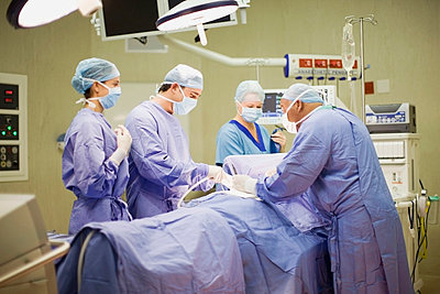 Doctor and nurses performing operation - p42914277f by Zero Creatives