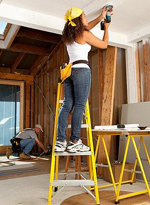 Hispanic woman using cordless drill - p555m1478409 by Tanya Constantine