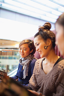 Young women reading menus in cafe - p924m836654f by NT Photography