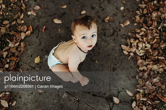 Baby toddler boy in diaper sitting with fall leaves at Halloween - p1166m2208361 by Cavan Images