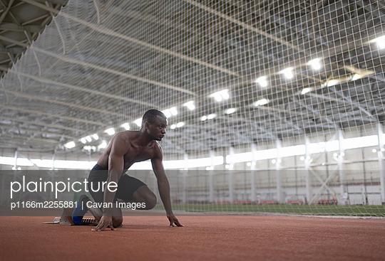African American athlete preparing to run near net - p1166m2255881 by Cavan Images