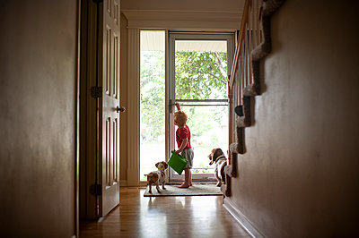 Young boy opening the front door for dogs at home while holding tablet - p1166m2146802 by Cavan Images