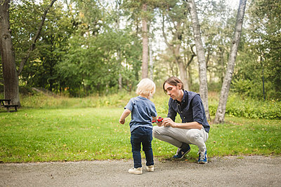 Father and son with toy car on footpath against plants at park - p426m2159423 by Maskot