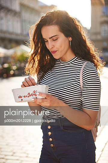 Smiling young woman eating strawberries in the city - p300m2012228 von gpointstudio