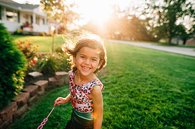 Little girl playing bubbles in yard during sunset - p1166m2073735 by Cavan Images