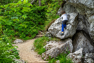 Young boy climbing a rock next to the trail during hike in the forest - p1166m2094283 by Cavan Images