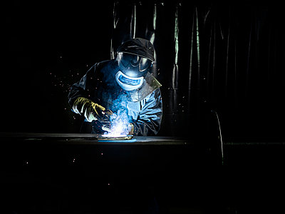 Industrial worker in protective clothing welding metal with welding torch - p300m2114082 by Christian Vorhofer