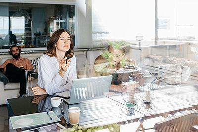Coworkers using laptop on table behind windowpane - p300m2144139 by Josep Rovirosa