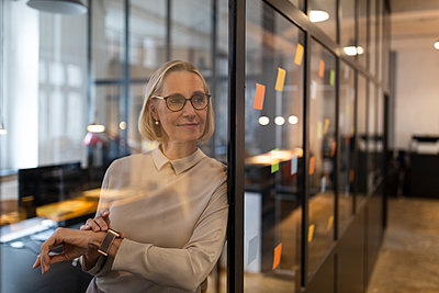 Mature businesswoman looking at adhesive notes on glass pane in office - p300m2156044 by Gustafsson