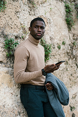 Young man using mobile phone while leaning on wall - p300m2251589 by Ezequiel Giménez