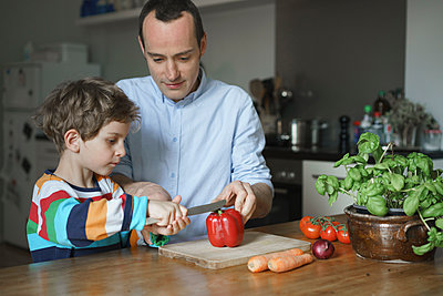 Father teaching son to cut vegetables at kitchen - p301m1148401 by Halfdark