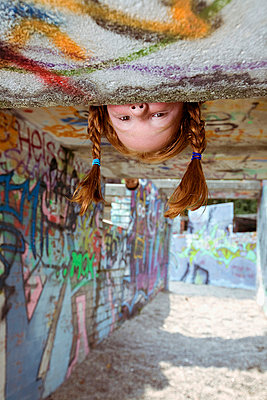red haired girl peeking at playground - p3165155 by beyond