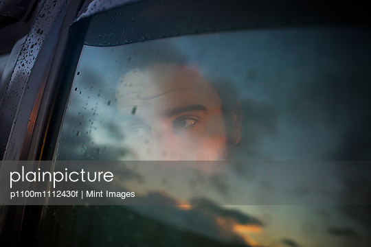 A man sitting in a car looking out. Reflections of the sunset sky on the window.