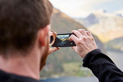 Mann fotografiert Geirangerfjord mit Smartphone - p1124m1503395 von Willing-Holtz