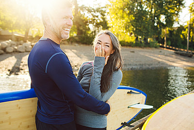 Happy couple with paddleboards standing at riverbank - p1166m1423474 by Cavan Images